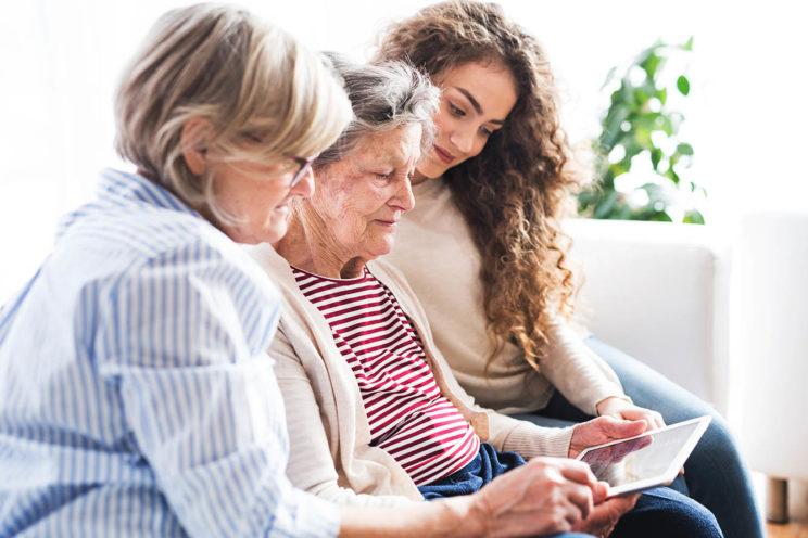 Äitä ja tytär opettamassa isoäidille tablet-tietokoneen käyttöä