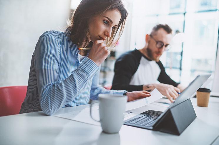 Nainen ja mies työskentelemässä toimistolla asiakirjojen parissa