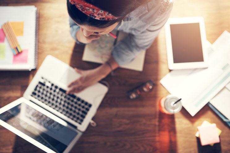 Nuori nainen kirjoittamassa kannettavalla tietokoneella työpöytänsä ääressä